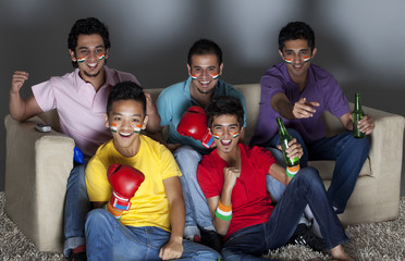 Excited young male friends watching boxing match together at home