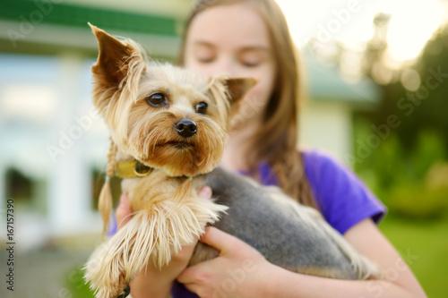 Cute Little Girl Holding Her Funny Yorkshire Terrier Dog Stockfotos