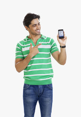Young man pointing to mobile phone