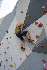 Mann beim Bouldern mit Helm auf Kletterwand outdoor