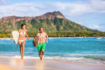 Happy surf people having fun surfing on Waikiki beach, Honolulu, Oahu, Hawaii. Asian woman, caucasian man multiracial couple running out of ocean splashing water. Summer vacations travel landscape.