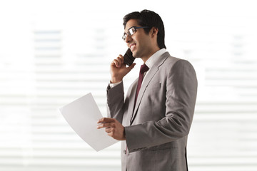 Smiling young businessman on phone call with a document