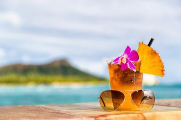 Hawaii mai tai cocktail drink on waikiki beach bar with flower, pineapple and sunglasses. View of the ocean and diamond head mountain in Honolulu, Hawaii. Summer vacation.