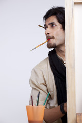 Handsome young artist with paintbrush in mouth contemplating
