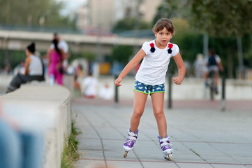 Little girl riding roller skates on the street
