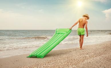 Boy with swimming mattress walks on sand sea beach