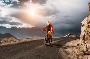 Tourist rides bike on road in Himalaya Mountain