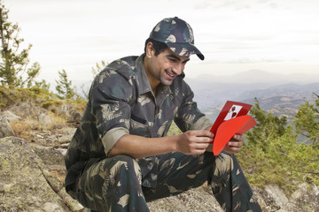 Smiling soldier reading greeting card while sitting on rock