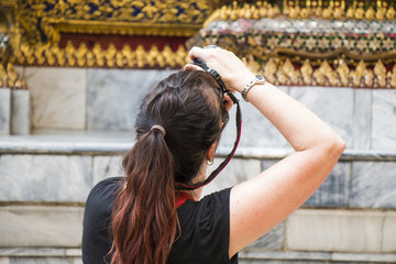 Woman taking photo of golden monument with dslr camera.
