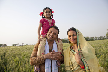 Portrait of a happy family in field with girl on father's shoulders