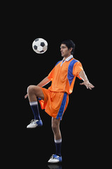 Male soccer player doing kick ups isolated over black background