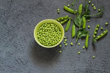 Green peas in bowl and on branches in pods