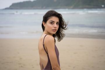 Slim girl in swimsuit on beach