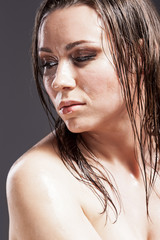 Beauty Concepts. Portrait of Sensual Tanned Caucasian Brunette Woman With Sad Expression with Wet and Shining Skin and Wet Hair. Against Dark Grey Background.