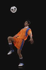 Happy male Indian soccer player doing kick ups isolated over black background