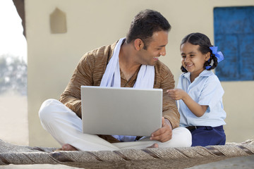 Indian father and daughter laughing over something while using laptop