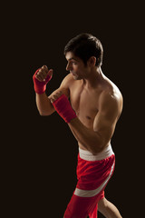 Side view of young male boxer standing against black background