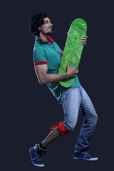 Full length of young man holding a skateboard like a guitar against black background