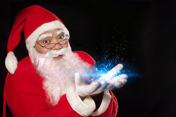 Close-up of Santa Claus performing magic over black background