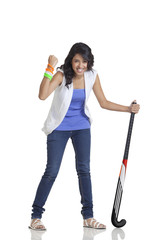 Full length portrait of happy young woman cheering with clenched fist while holding hockey stick over white background