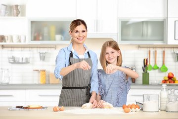 Happy mother and daughter preparing dough in kitchen