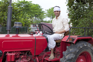 Portrait of a farmer with a laptop sitting on a tractor