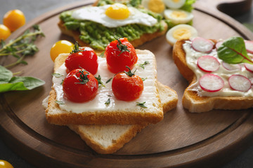 Different tasty breakfast toasts with vegetables on wooden board