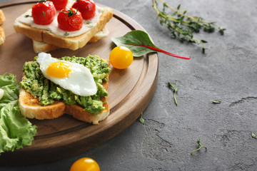 Different tasty breakfast toasts with vegetables on table