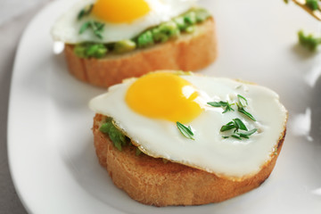 Tasty breakfast toasts with avocado and quail eggs on plate, closeup