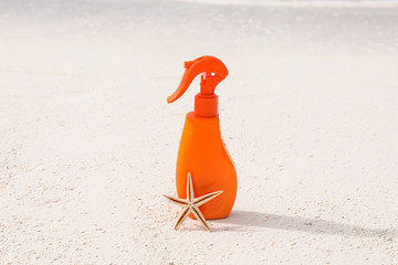 Bottle with sunscreen cream and starfish on sea shore. Summer vacation concept