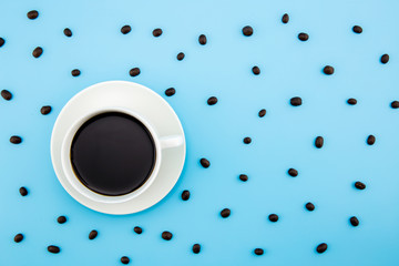 Stylish set: coffee beans on pastel and coffee cup blue background. Flat lay. Top view.
