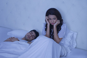 Sad woman sitting in bed with snoring man