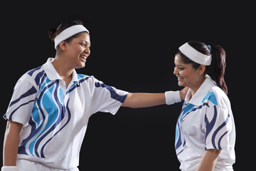 Happy young female players talking to each other against black background