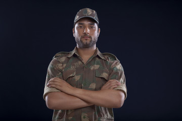 Portrait of a soldier standing with his arms crossed over blue background