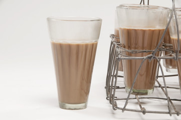 Glass of chai kept besides grid tray over white background