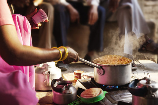 Cropped image of female vendor preparing chai on stove with customers in background