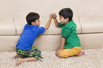 Brothers arm wrestling on sofa in living room