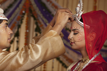 Bengali groom putting sindoor on brides forehead