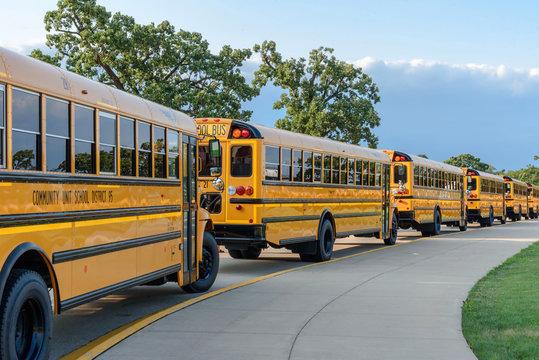 school bus line in parking lot of high school