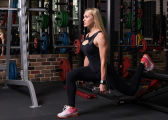 Fitness woman doing lunge squat exercise with a box in the gym