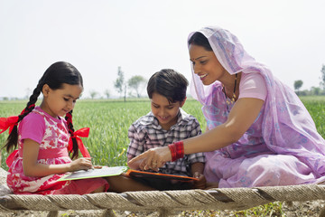 Happy mother guiding children with their homework