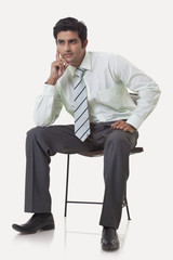 Full length of young male executive contemplating over white background