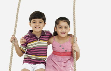 Portrait of boy and girl sitting on a swing