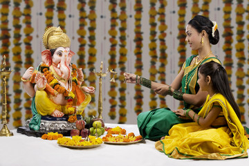 Mother and daughter performing a pooja