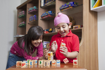 Happy brother and sister playing with wooden toy blocks