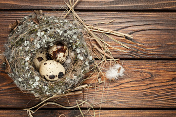 quail eggs in a nest over old wooden background top view