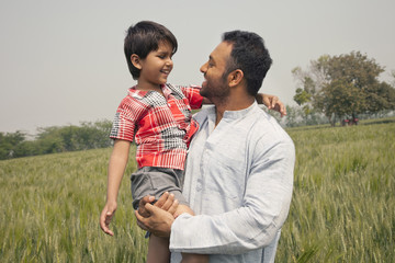 Happy father and son looking at each other with wheat field in background