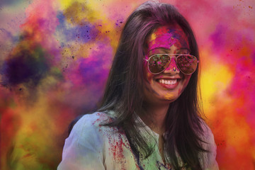Portrait of a smiling girl with mirror sunglasses covered with colorful Gulal powder during a Holi festival