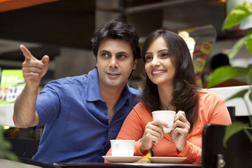 Man showing something to wife while having tea in shopping mall