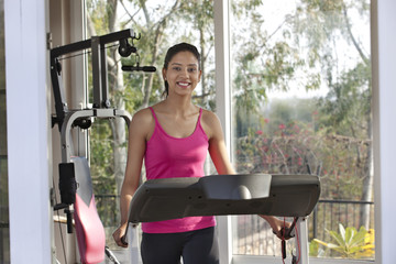 Portrait of happy young woman smiling while exercising on a treadmill
